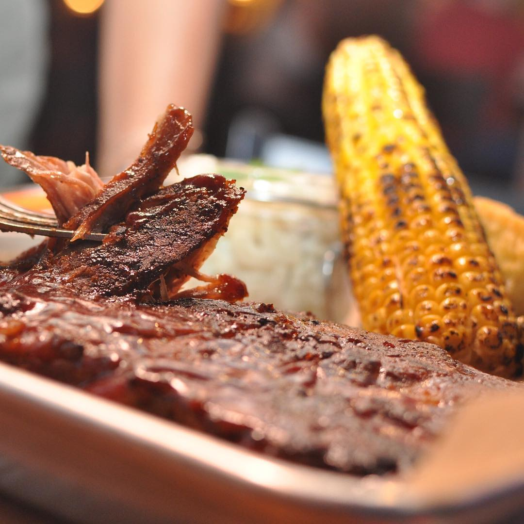 It's DINNER TIME! 🍽 Half rack of tender fall off the bone Carolina BBQ ribs served with grilled corn ,Whiskey butter, macaroni salad and fall apart corn bread