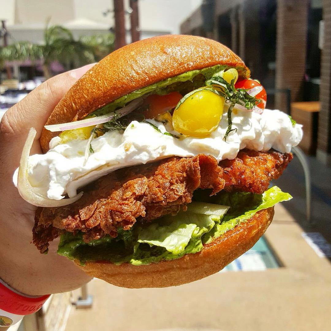 This Crispy chicken sandwich with buratta, heirloom tomatoes and pesto perfected by @chefmarcmarrone looks like HEAVEN on a bun!! 😜